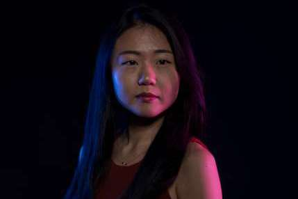 Kyulim Lee poses for a photo against a dark backdrop, her face illuminated with colored light.