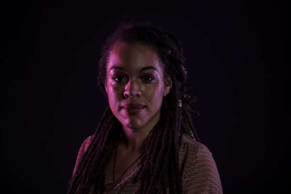 Olivia Bailey poses for a photo against a dark backdrop, her face illuminated with colored light.