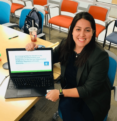 Ashley Zuniga poses for a photo with a laptop in a classroom.