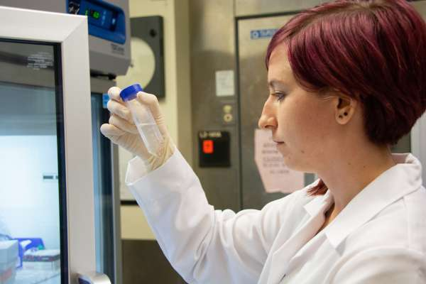 Shelby Blaes examines a test tube in a laboratory.