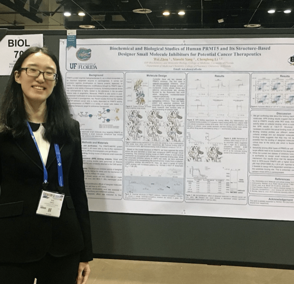 Wei Zhou stands in front of her research poster.