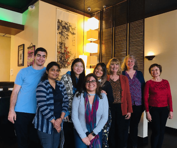 Eight people stand and pose for a photo inside a restaurant.