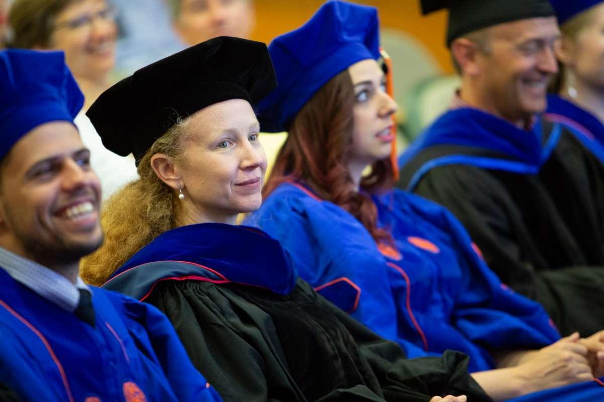 Graduates sit in an auditorium.