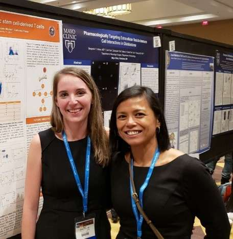 Bayli DeVita Dean and Catherine Flores pose for a photo in front of a research poster.