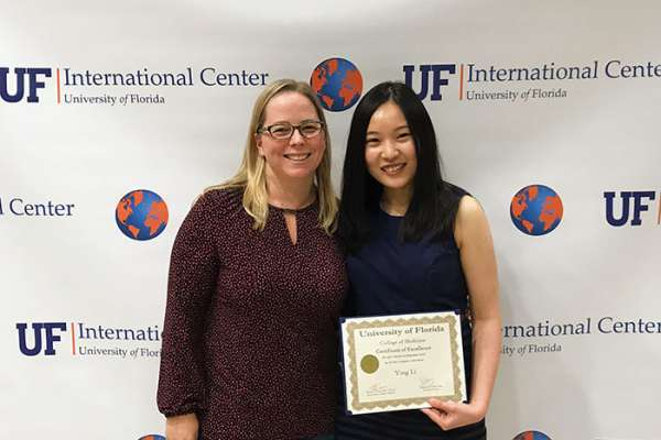 Ying Li holds an award and poses for a photo with a woman.