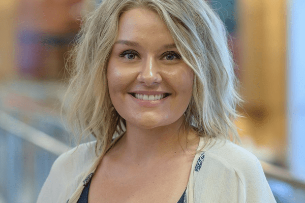 A woman with short blond hair smiles at the camera while standing indoors.