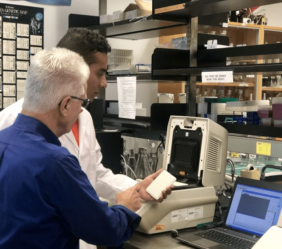 Mario Chang works in the lab with his mentor.