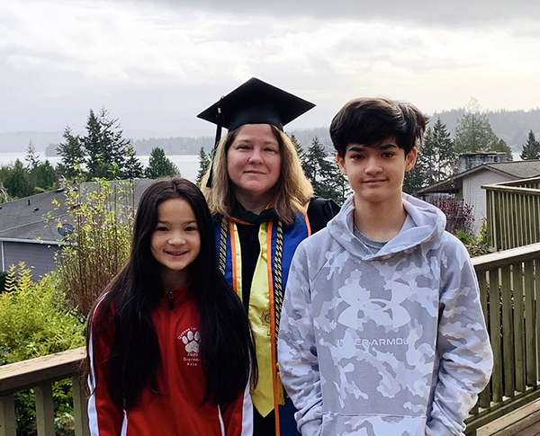 Inga Oberst wears graduation regalia while standing outside with her two children.