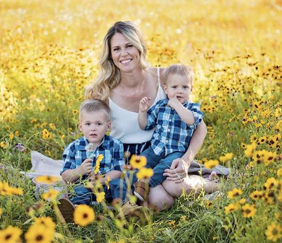 Kristin Watts sits in a field of sunflowers while holding her two young sons.