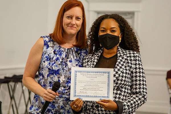 Student Brittny Randolph poses for a photo with a faculty member.