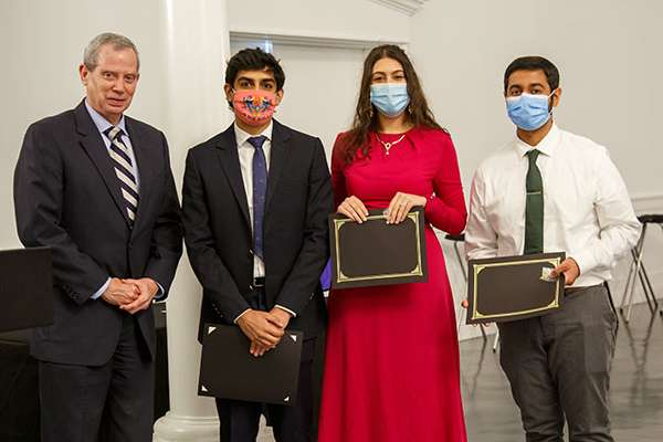 Three students pose for a photo with Doctor Duff.