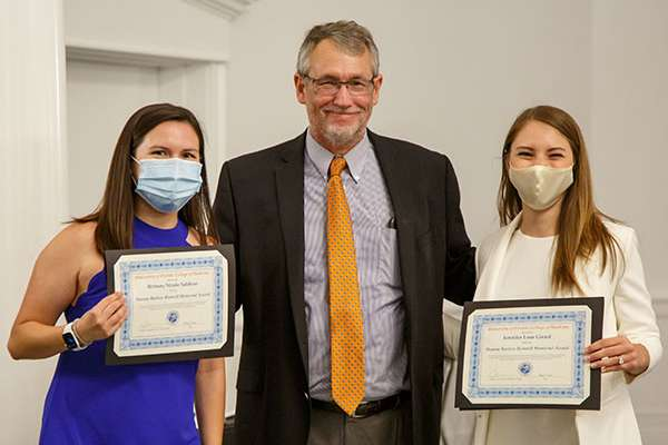 Two students pose for a photo with Doctor Lynch.