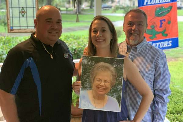 Brian Palmer (right), with his two children, Jillian Johnson and Joshua Palmer, pictured here holding a photo of his mother, the late Lee Berkowitz-Palmer.
