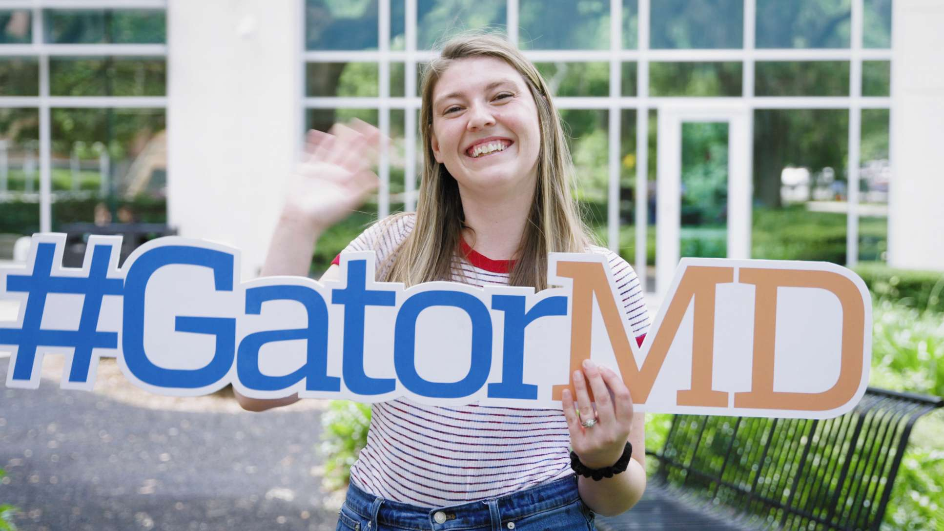 """A student waves while holding a sign that says """"Gator M-D."""""""