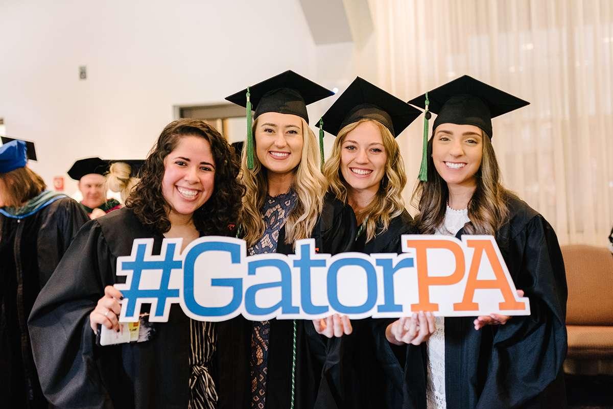 Four graduates hold a sign that says hashtag Gator P-A.